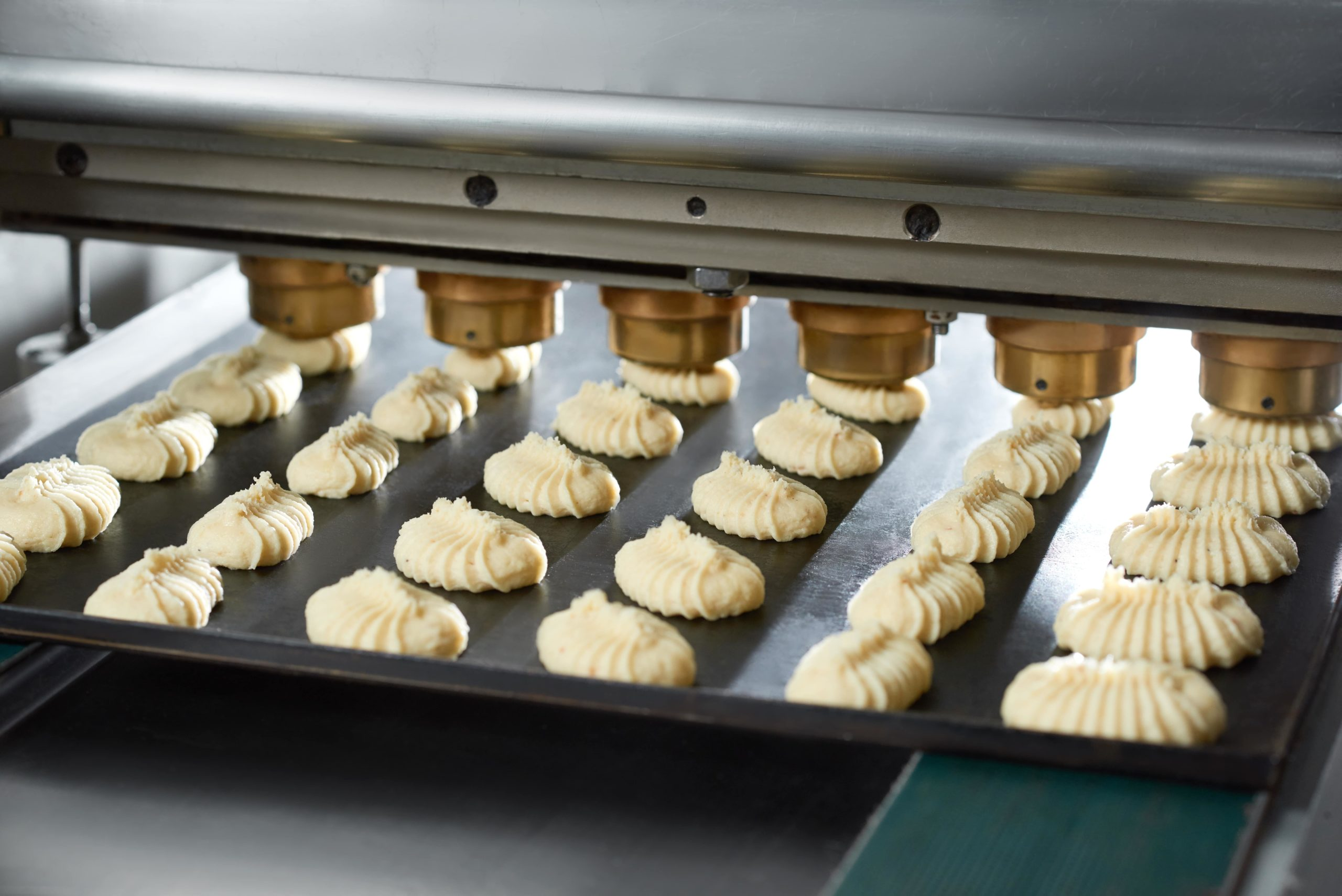 close-up-conveyor-line-s-equipment-making-little-identical-cakes-from-raw-dough-they-lie-black-dish-conveyor-line-bakery-min