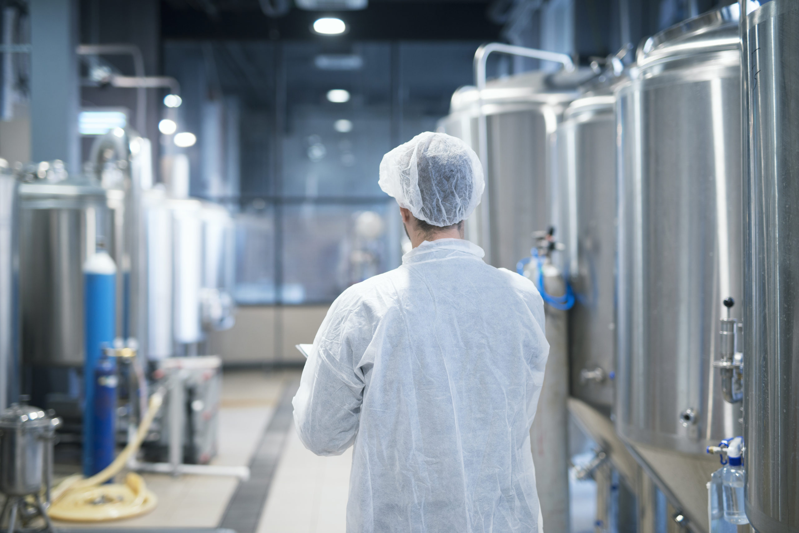 Technologist in white protective suit walking through food factory production line checking quality.